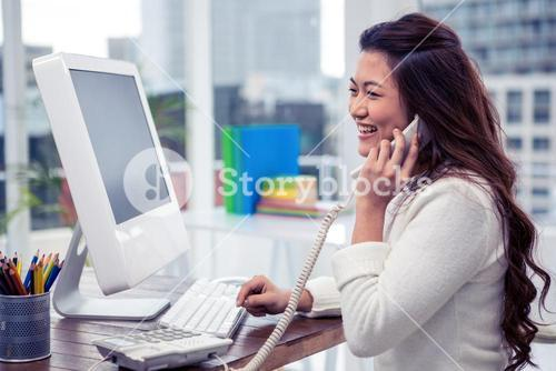Smiling Asian woman on phone call using computer