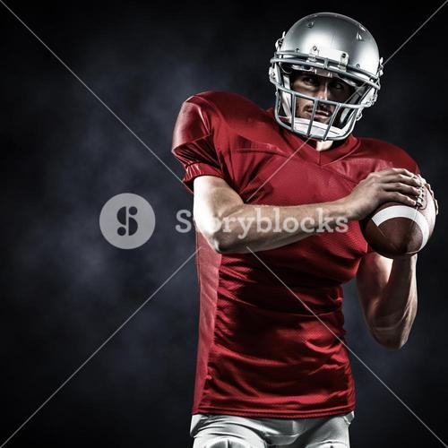 Composite image of confident american football player in red jersey holding ball