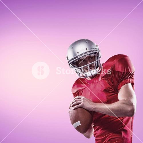 Composite image of american football player in red jersey looking away while holding ball