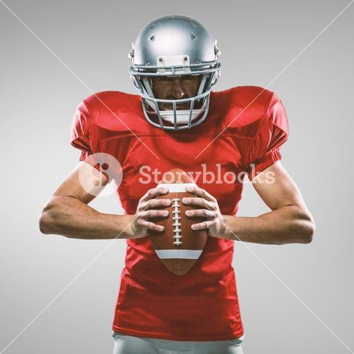 Composite image of furious american football player in red jersey and helmet holding ball