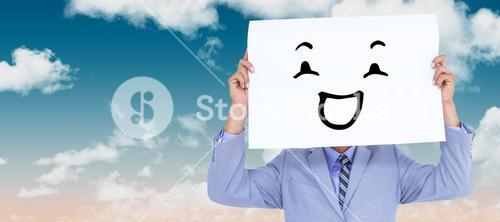 Composite image of  portrait of a businessman hiding his face behind a blank panel