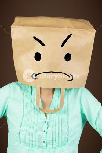 Composite image of woman with hands on hip and covering head with brown paper bag