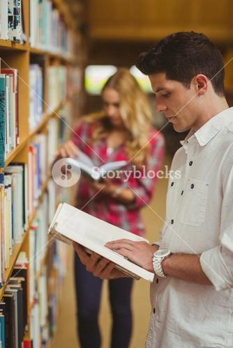 Concentrated male student reading book