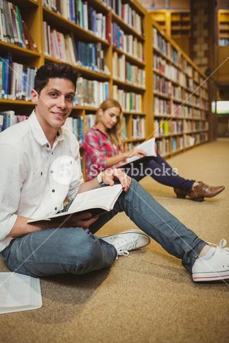 Smiling male student revising on floor