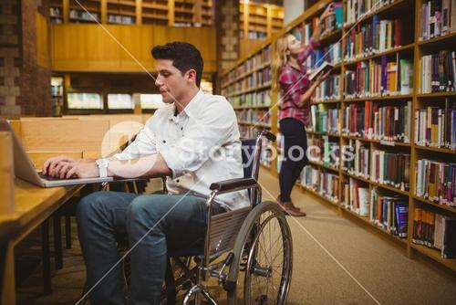 Student in wheelchair typing on his laptop while woman searching books