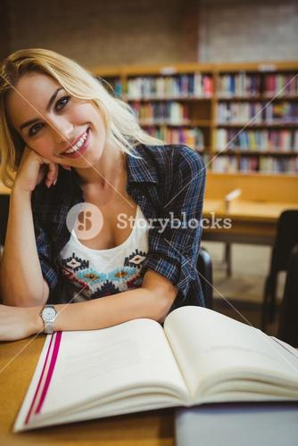 Smiling student reading a book at table
