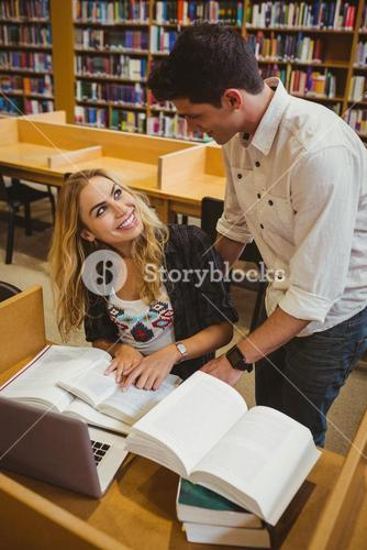 Smiling students working together while sitting at table