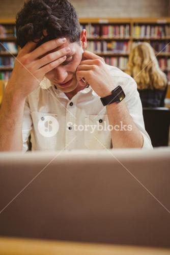 Focused student using his laptop while working