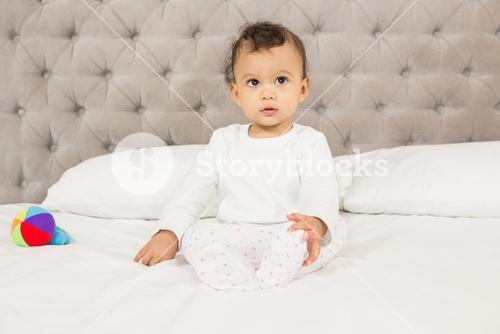 Cute baby sitting on bed