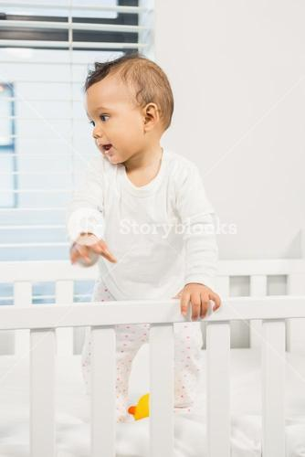 Cute baby standing in the crib