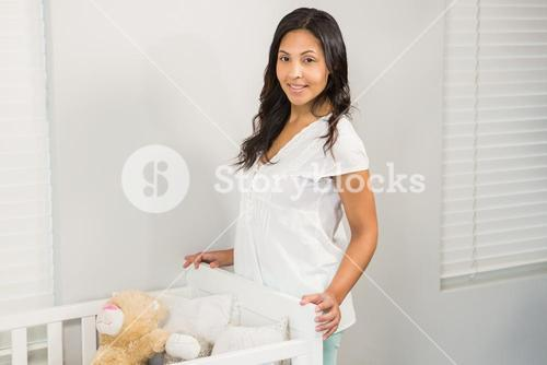 Smiling brunette standing near the crib
