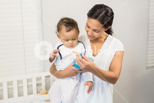 Smiling brunette feeding baby