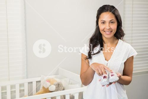 Smiling brunette holding baby shoes