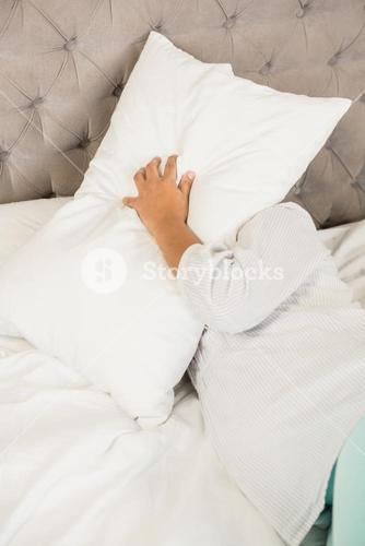 Pregnant woman covering face with pillow