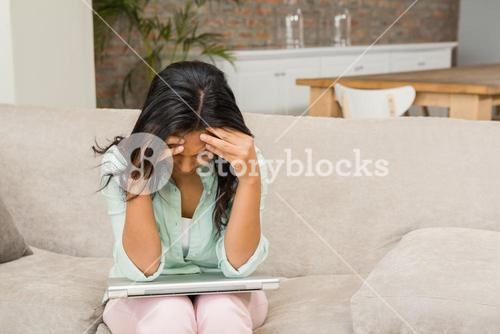 Worried brunette with closed laptop on her legs