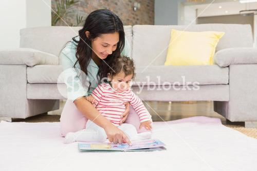 Happy mother with her baby looking at a book