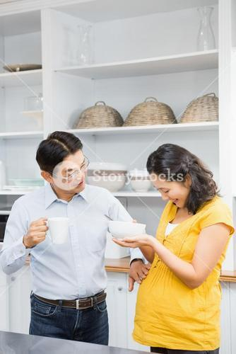 Happy expectant couple in the kitchen