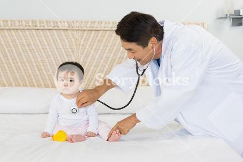 Cute baby being visited by doctor