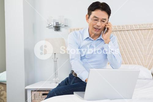 Man on a phone call using laptop