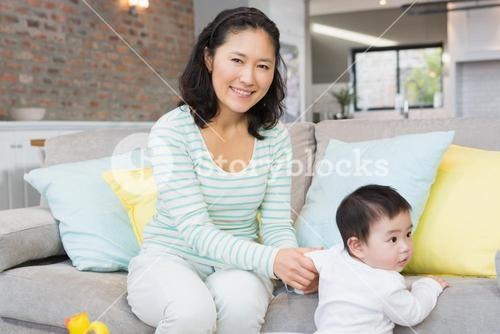 Happy mother with baby daughter in the living room
