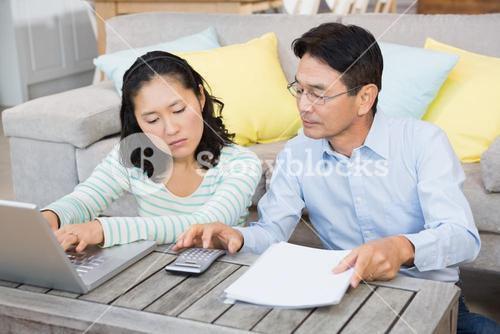 Worried couple checking bills