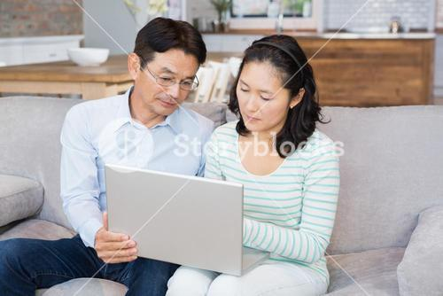 Serious couple using laptop