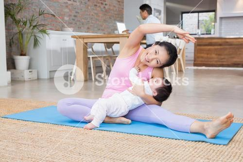 Happy mother and baby daughter exercising on mat