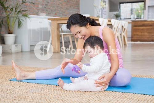 Happy mother and baby daughter sitting on exercising mat