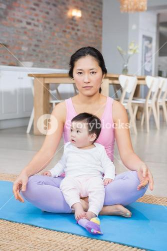 Serious woman sitting on mat with baby daughter