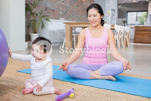 Calm mother sitting on mat at home