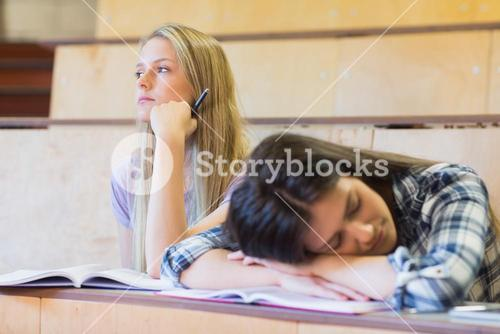 Bored student listening while classmate sleeping