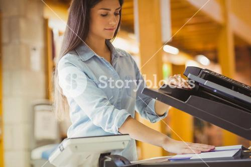 Smiling brunette student making a copy