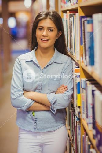 Smiling brunette student standing next to bookshelves with arms crossed