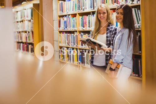 Pretty young students working together with book