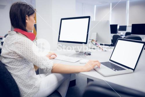 Rear view of student using computer