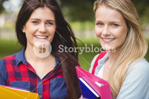 Smiling students holding binder