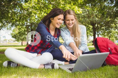 Smiling students using laptop