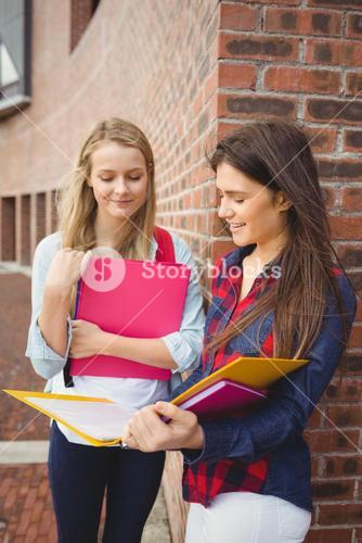 Smiling students reading book