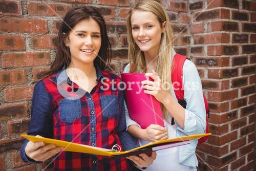Smiling students with binder looking at camera