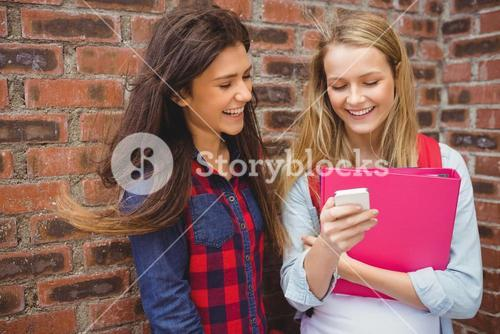 Smiling students using smartphone