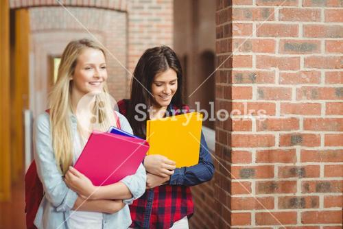 Smiling students with books in the hallway