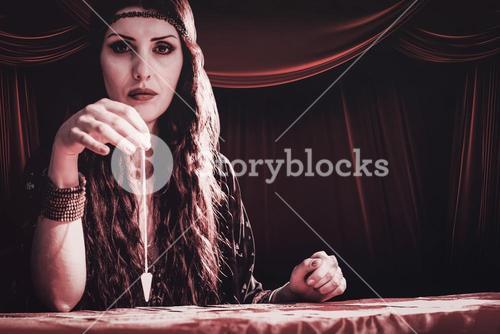 Composite image of portrait of fortune teller with pendulum