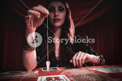 Composite image of female fortune teller holding pendulum with eyes closed