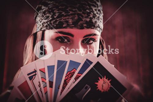 Composite image of fortune teller using tarot cards