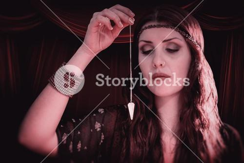 Composite image of fortune teller holding pendulum with eyes closed