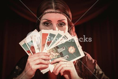 Composite image of portrait of fortune teller hiding mouth with tarot cards