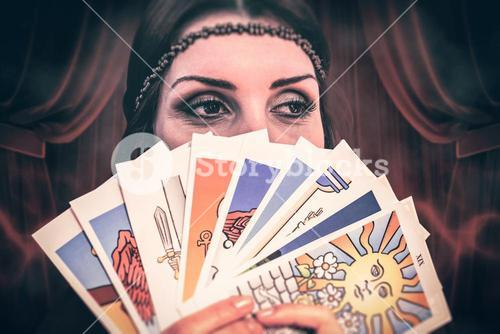 Composite image of fortune teller holding tarot cards while looking away