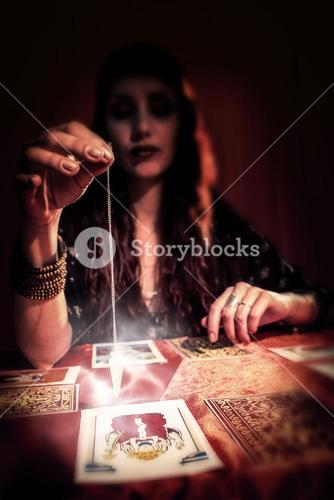 Composite image of female fortune teller using pendulum