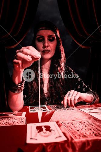 Composite image of female fortune teller looking at pendulum