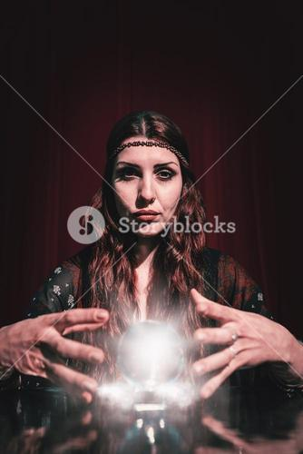 Composite image of portrait of serious fortune teller using crystal ball
